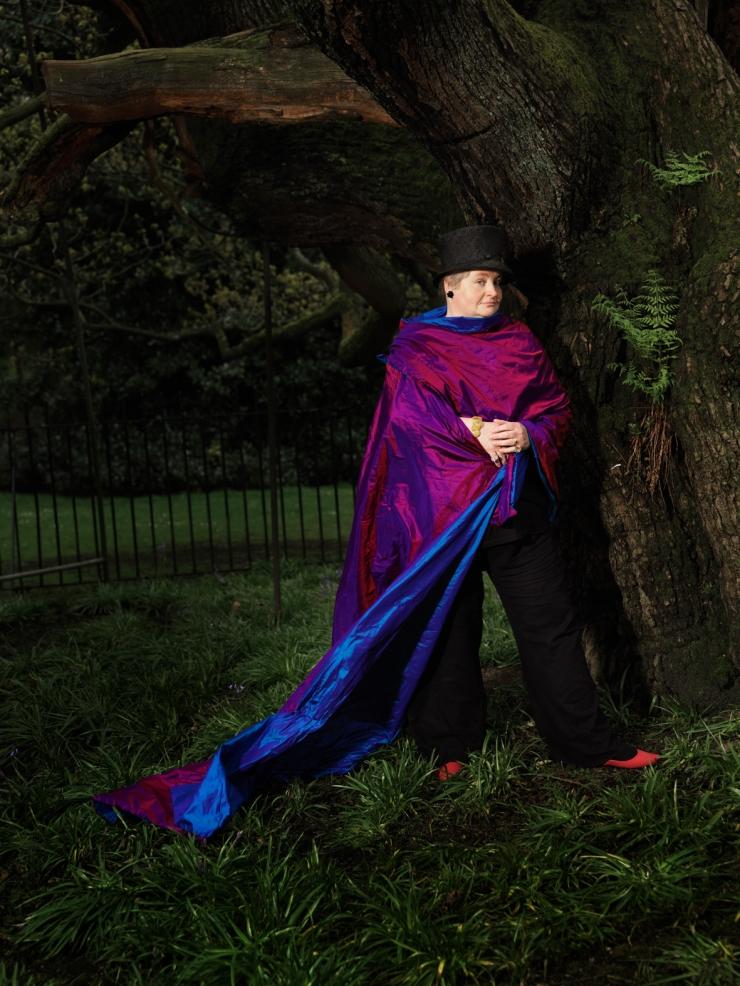 Woman in silk stole standing by ancient oak tree