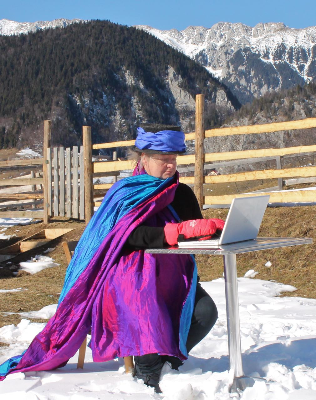 Author typing in snow, mountains, gloves
